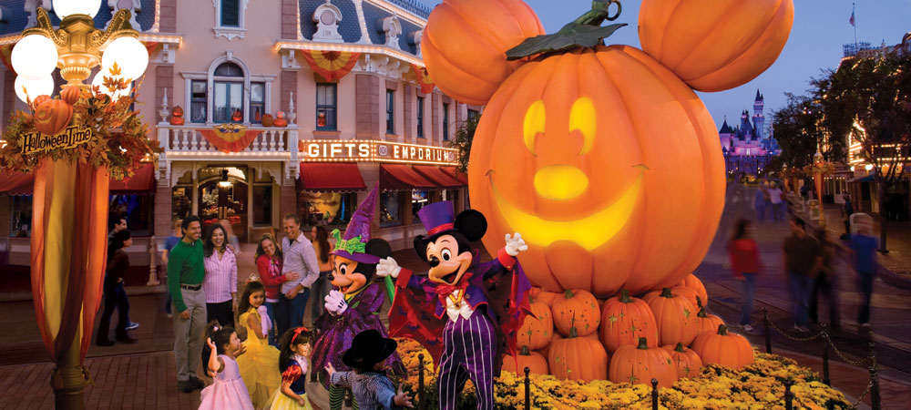 Mickey and Minnie Greet Guests In Front of a Giant Mickey Pumpkin