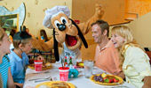 A family enjoys a meal and Pluto's company.
