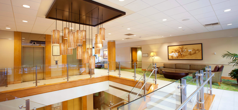 An elegant yellow glass chandelier hangs over the lobby's open stairwell.