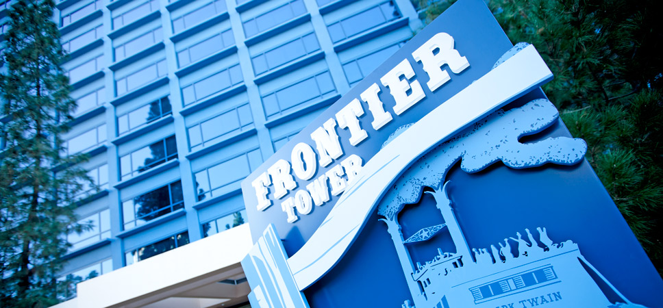 The Frontier Tower sign with an illustration of the Mark Twain Riverboat attraction.
