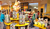 Guests look at Disney merchandise on the Fantasia Shop shelves.