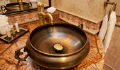 Copper-designed sink set on a marble counter.