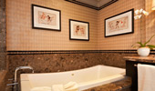The sophisticated bathtub area is decorated in beige, brown and beautiful marble.