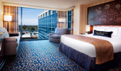 King-size bed next to view of blue-tinged glass that envelops the reinterpreted Resort hotel.
