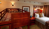 The view of the top bunk, also decorated with warm reds and wood