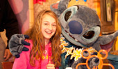 A girl poses for photos with the Disney Character Stitch.