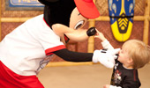 A toddler touches the tip of Mickey's nose; Mickey touches the toddler's nose.