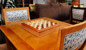 The wood table by the window has a matching wood checkers and chess board.